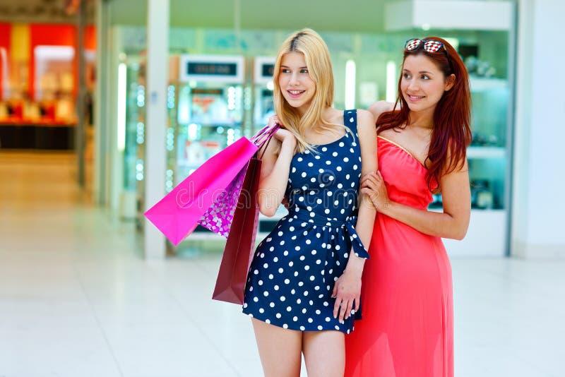 Två kvinnavänner i shoppinggalleria med påsar royaltyfria foton