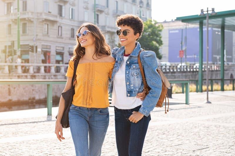 Två kvinnavänner som går på gatan royaltyfri bild