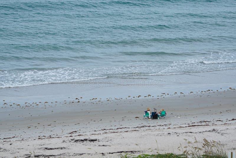 Två kvinnavänner som har coctailar på stranden arkivfoto