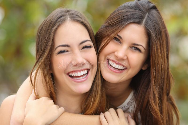 Två kvinnavänner som skrattar med perfekta vita tänder arkivfoto