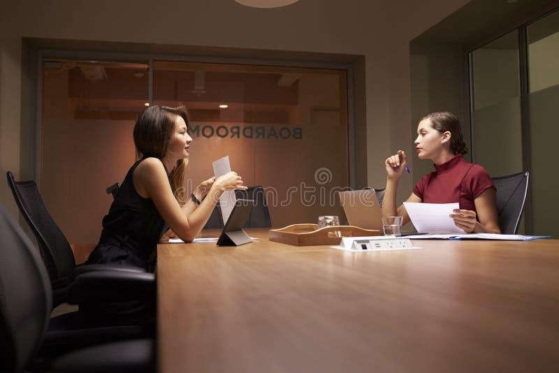 Två kvinnliga affärskollegor som sent arbetar i ett kontor arkivbild