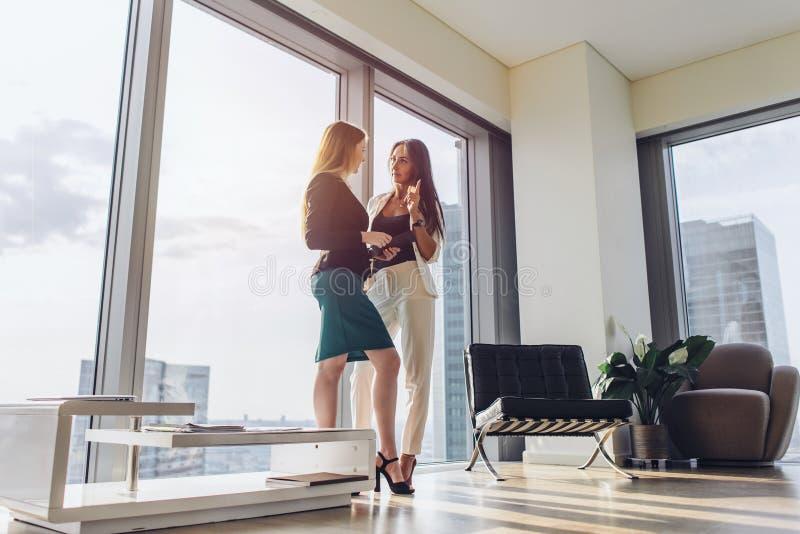 Två kvinnliga affärspartners som diskuterar plan som står i modernt kontor på tornkvarteret fotografering för bildbyråer