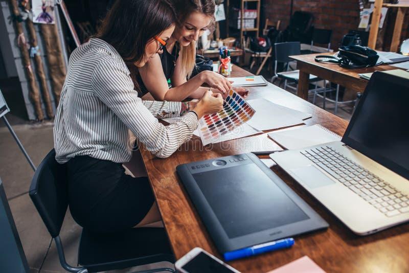 Två kvinnliga arkitekter som arbetar tillsammans genom att använda färgprovkartor som sitter på skrivbordet med bärbara datorn, g royaltyfri fotografi