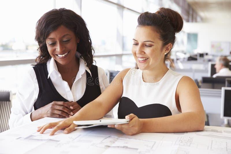 Två kvinnliga arkitekter som tillsammans i regeringsställning arbetar på ett skrivbord royaltyfri fotografi