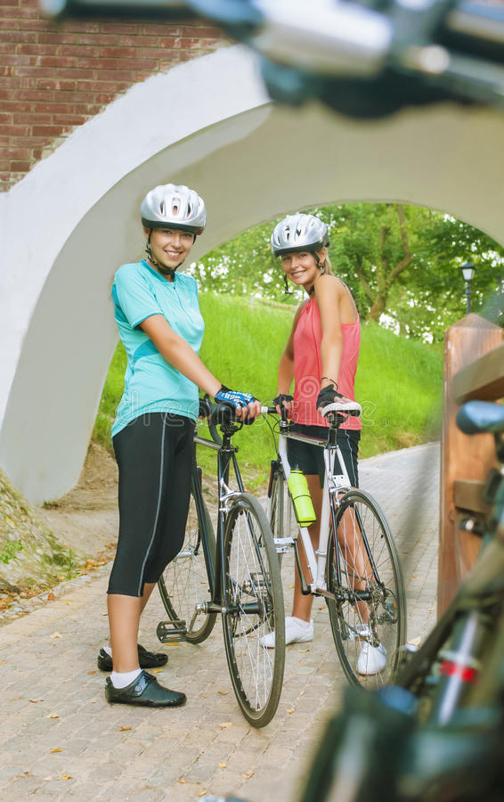 Två kvinnliga Caucasian cyklister som står le utomhus arkivbild