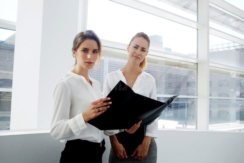 Två kvinnliga disponenter som betraktar pappers- dokument i mapp, medan stå i regeringsställning inre, fotografering för bildbyråer