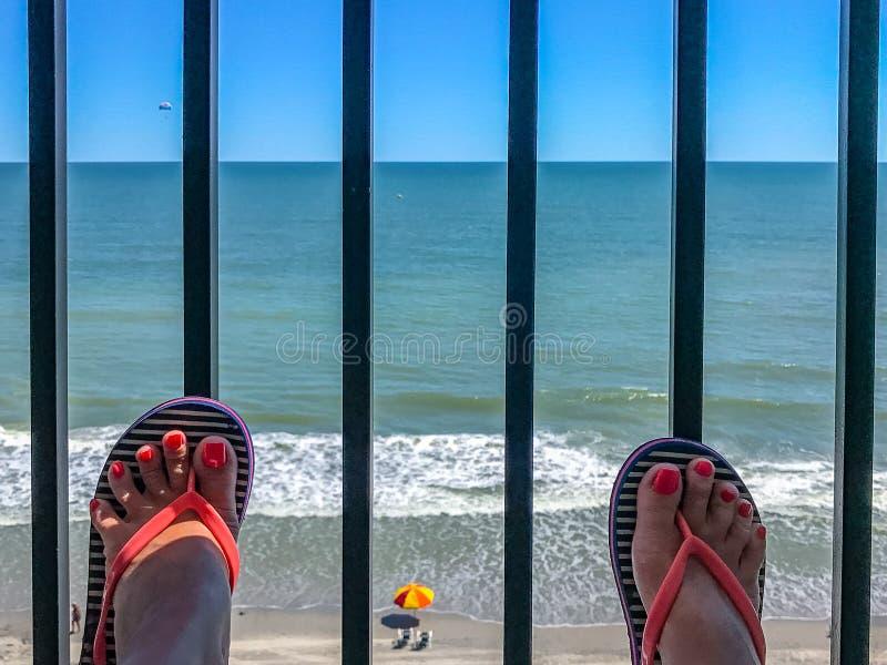 Två kvinnliga fot med en pedikyr mot bakgrunden av den beachfront strandpromenaden Myrtle Beach South Carolina för hav arkivbild