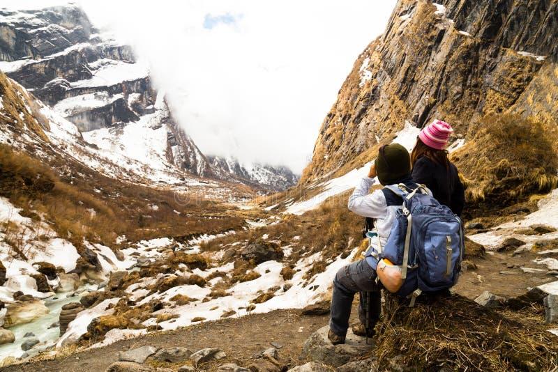 Två kvinnliga fotvandrare som vilar, medan tycka om den fridfulla sikten av den snöig treken arkivbild