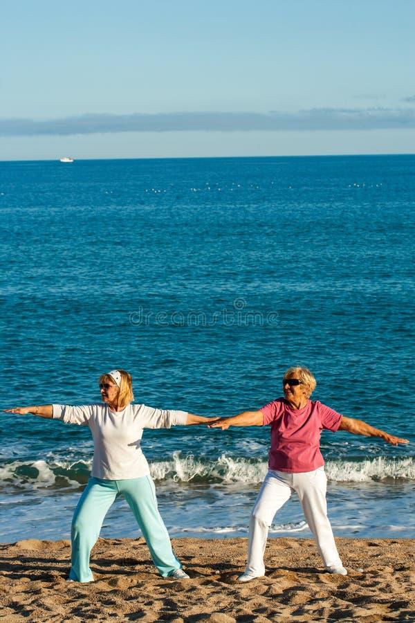 Två kvinnliga guld- agers som gör yoga på stranden. fotografering för bildbyråer