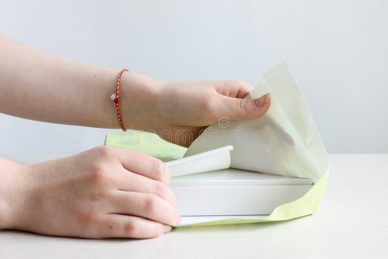 Två kvinnliga händer tar av att förpacka från askar på en ljus bakgrund fotografering för bildbyråer