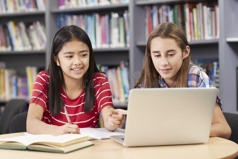 Två kvinnliga högstadiumstudenter som arbetar på bärbara datorn i arkiv royaltyfri foto