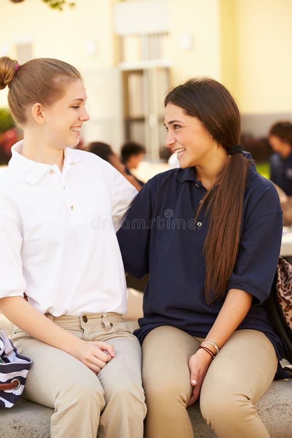 Två kvinnliga högstadiumstudenter som bär likformign arkivfoto