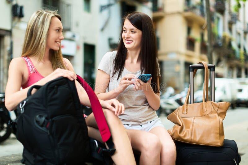 Två kvinnliga handelsresande som använder smartphonen som navigerar systemet fotografering för bildbyråer