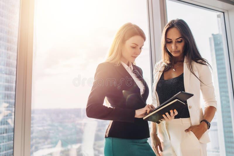 Två kvinnliga kollegor med minnestavladatoren, medan stå i regeringsställning bygga royaltyfri fotografi