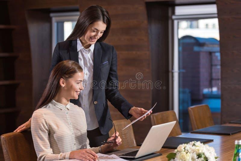 Två kvinnliga kollegor som diskuterar deras projekt royaltyfria bilder