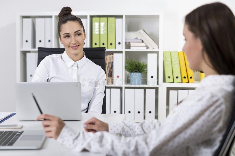 Två kvinnliga kollegor som till varandra ler i ett kontor arkivfoto