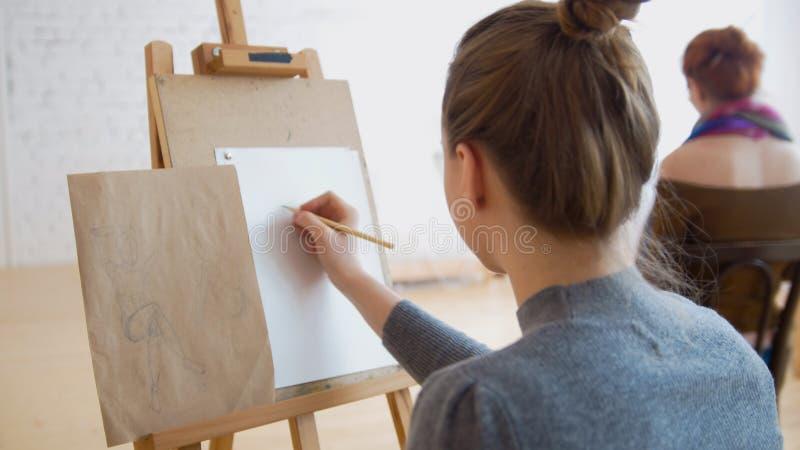 Två kvinnliga konstnärer som skissar modellen i ljus teckningsgrupp royaltyfri foto