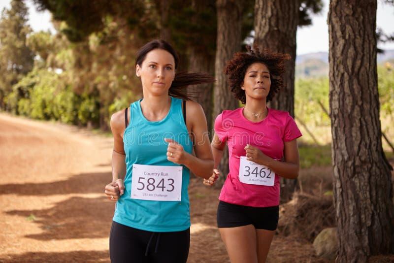 Två kvinnliga löpare i ett lopp arkivfoto
