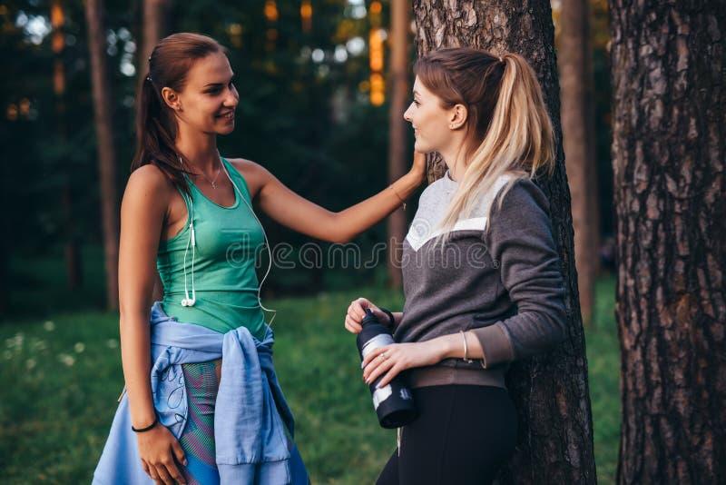 Två kvinnliga löpare som kopplar av efter genomkörareanseende nära trädet som in talar, parkerar royaltyfria bilder