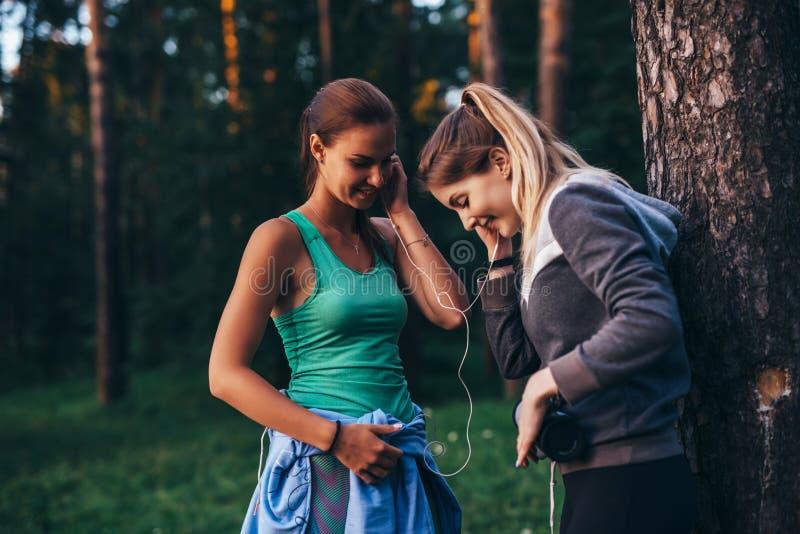 Två kvinnliga löpare som kopplar av efter genomkörareanseende nära trädet som in talar, parkerar fotografering för bildbyråer