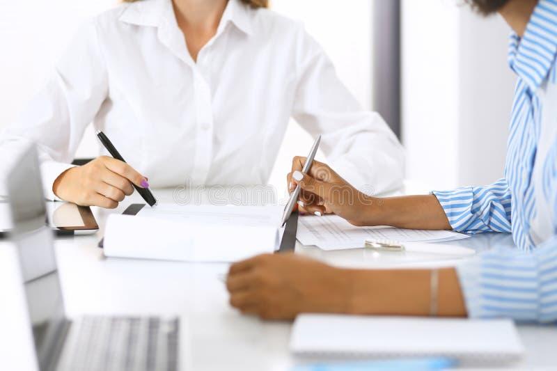 Två kvinnliga revisorer som kontrollerar bokföringsunderlag eller räknar vid räknemaskininkomst för skattformen, händer på mötet arkivbild