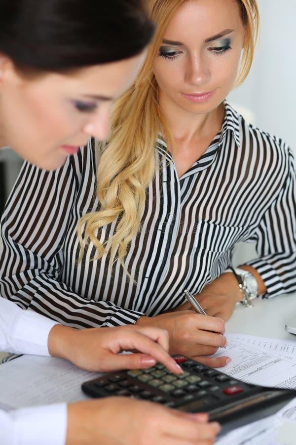 Två kvinnliga revisorer som räknar på räknemaskinen fotografering för bildbyråer