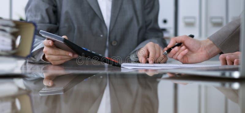 Två kvinnliga revisorer som räknar på räknemaskininkomst för avslutning för skattform, handcloseup Skattemyndigheten royaltyfria bilder