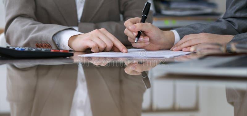 Två kvinnliga revisorer som räknar på räknemaskininkomst för avslutning för skattform, handcloseup Skattemyndigheten arkivbilder