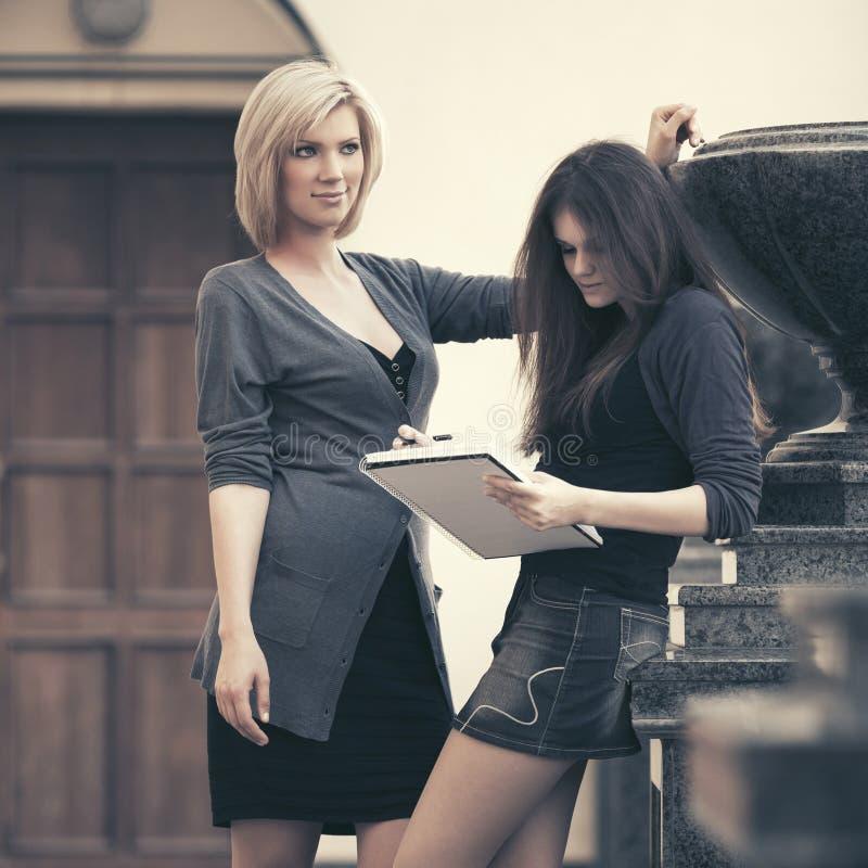 Två kvinnliga studenter för barnmode på universitetsområdet royaltyfria foton