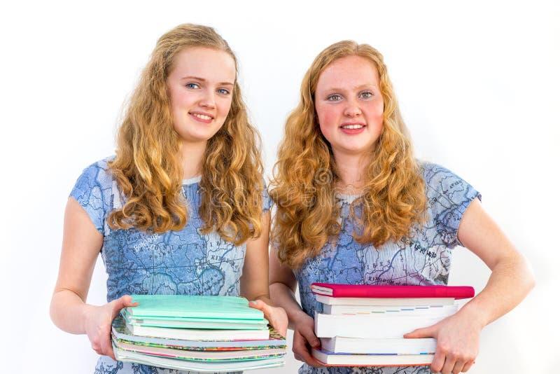 Två kvinnliga studenter som rymmer studieböcker arkivfoton