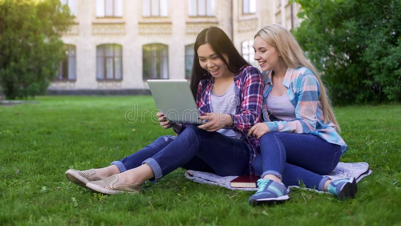 Två kvinnliga studenter som sitter på gräs och att skratta på bilder i bärbara datorn som shoppar arkivbilder