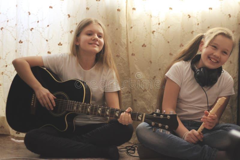 Två kvinnliga tonår som hemma spelar musikinstrument arkivfoto