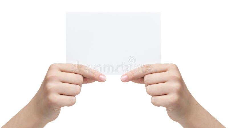 Två kvinnliga tonåriga händer som rymmer det pappers- arket royaltyfri foto