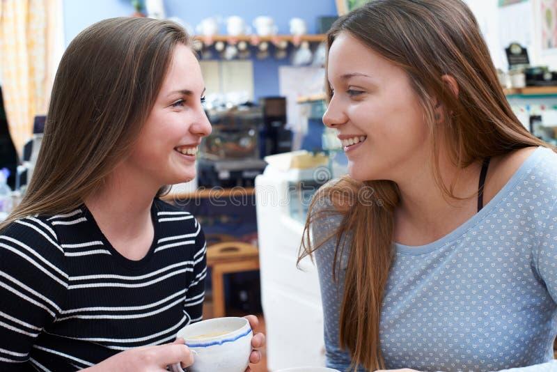 Två kvinnliga tonårs- vänner som möter i kafé royaltyfria foton