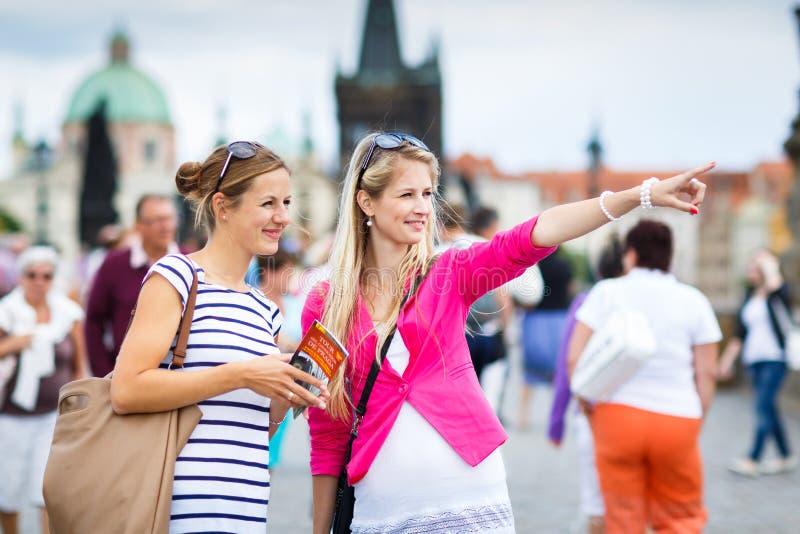 Två kvinnliga turister som går längs Charlesen, överbryggar royaltyfri foto