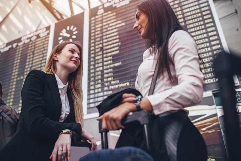 Två kvinnliga turister som står near informationsskärm om flyg i internationell flygplats royaltyfria foton