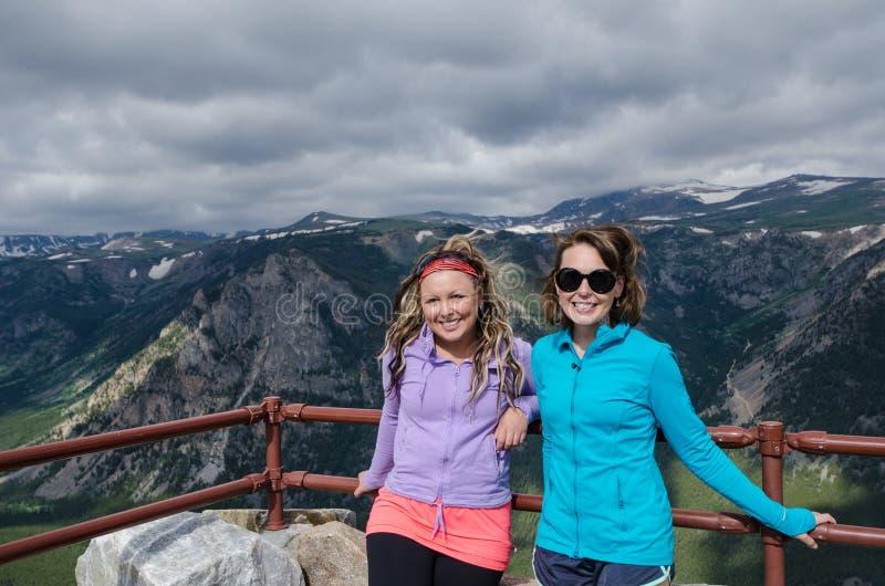 Två kvinnliga vän20-tal att posera tillsammans på förbiser längs Montana Beartooth Pass arkivbild