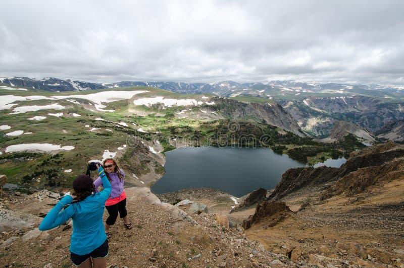 Två kvinnliga vän20-tal att ta bilder av de på förbiser i bergen av Montana arkivbilder