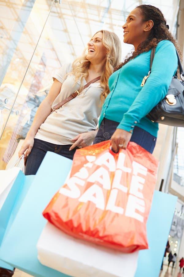 Två kvinnliga vänner med påsar i shoppinggalleria royaltyfri bild