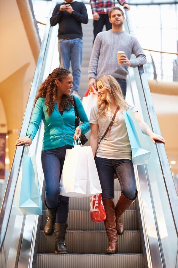 Två kvinnliga vänner på rulltrappan i shoppinggalleria royaltyfri bild