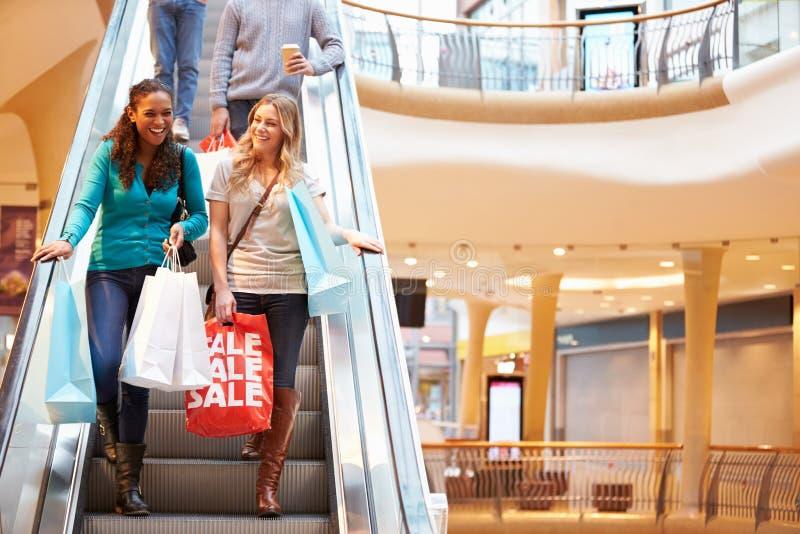 Två kvinnliga vänner på rulltrappan i shoppinggalleria arkivfoton