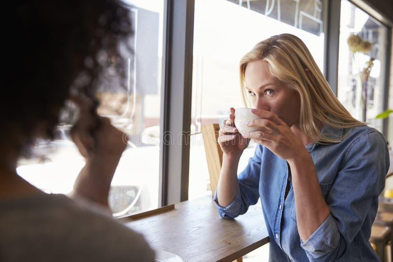 Två kvinnliga vänner som möter i coffee shop royaltyfri foto
