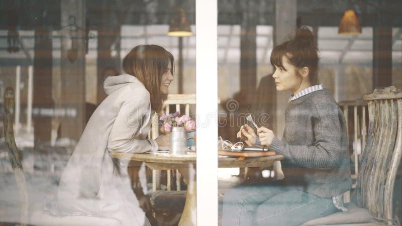 Två kvinnliga vänner som möter i ett kafé för att tala royaltyfri foto