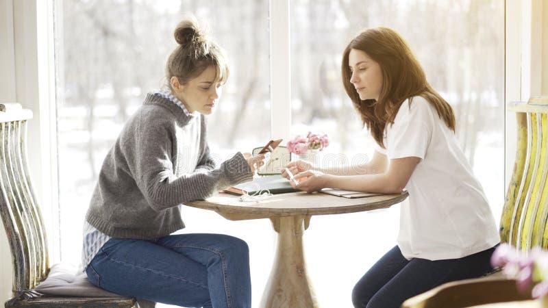 Två kvinnliga vänner som sitter i en kaféframsida - till - framsida arkivbild