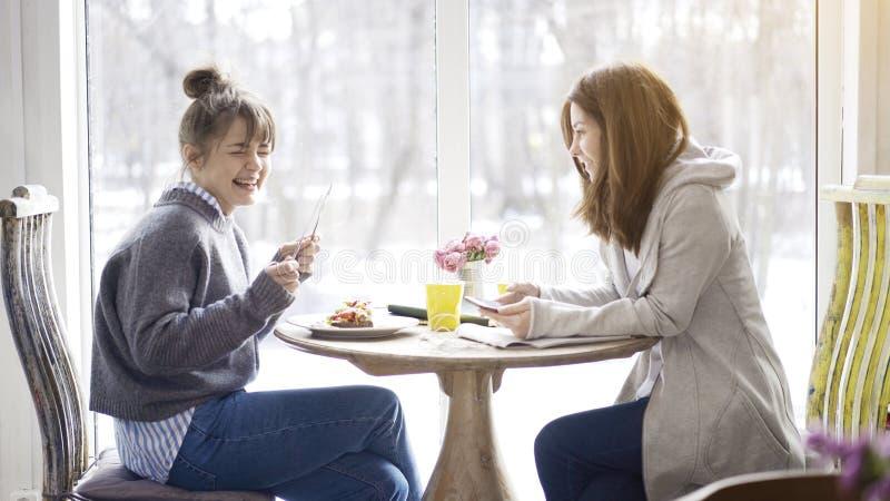 Två kvinnliga vänner som talar att skratta i ett kafé royaltyfria bilder