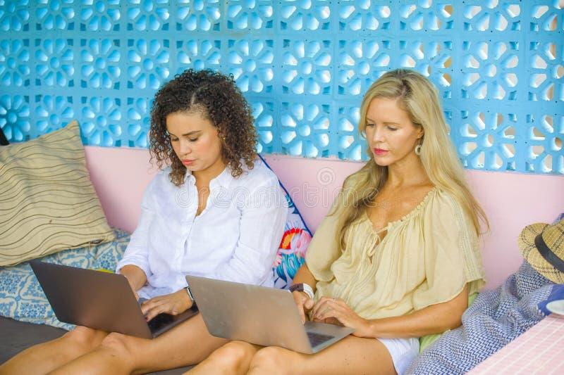 Två kvinnliga vänner som tillsammans utomhus arbetar på det kalla kafét med bärbar datordatoren, en flickacaucasian, det annat af fotografering för bildbyråer