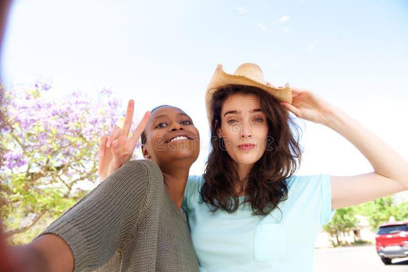 Två kvinnliga vänner som utanför tar selfie royaltyfria bilder