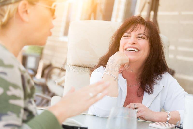 Två kvinnliga vänner som utanför tycker om konversation royaltyfria bilder