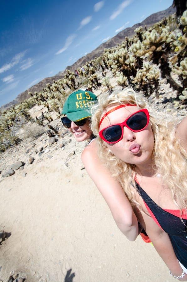 Två kvinnliga vänner tar en selfie på den Cholla kaktusträdgården i Joshua Tree National Park arkivbilder