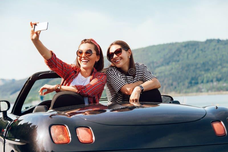 Två kvinnliga vänner tar ett selfiefoto i cabriolrtbil under t royaltyfria foton